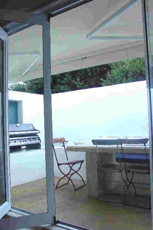 Retractable Awnings - Folding Arm awning in white over private patio area in Waiheke Island copy.jpg