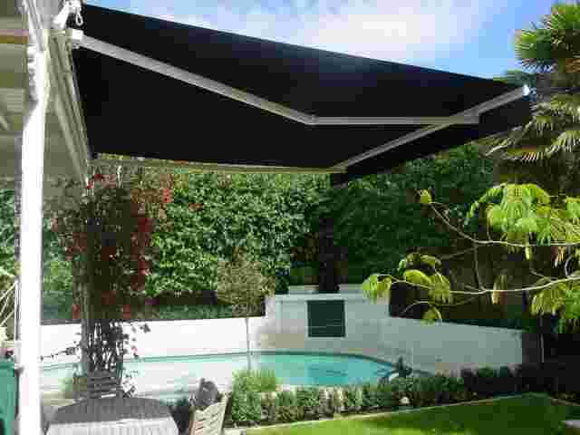 Retractable Awnings - Folding Arm awning in black canvas over pool patio in Freemans Bay copy.JPG