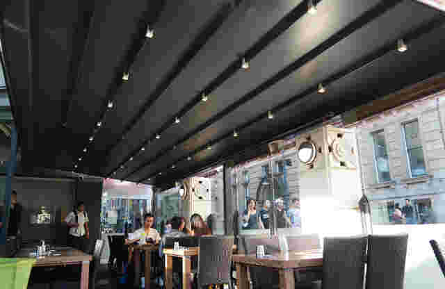Retractable Roof - Oztech Retractable Roof over outdoor dining area with Black Fabric